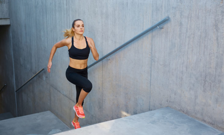 Athletic woman running up stairs during cardio - interval training